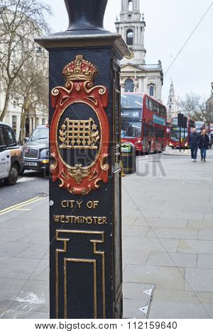 LONDON, UK - DECEMBER 20: Detail of light post in front of Sommerset House depicting the City of Westminster coat of arms and red double-decker bus in the background. December 20, 2015 in London.
