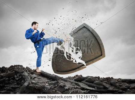 Young determined karate man breaking concrete shield
