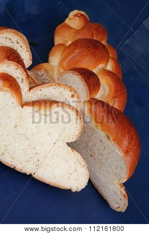 baked product : cutted golden challah on blue wooden table