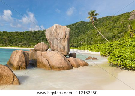 Beautifully shaped granite boulders in the turquoise sea  and a perfect white sand at Anse Coco, La Digue island, Seychelles. Panorama