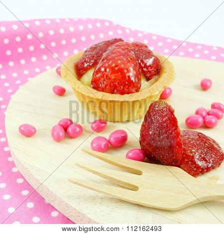 Delicious home baked strawberry tart and small pink chocolate candies