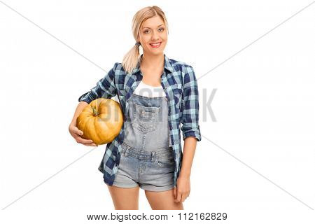 Young cheerful woman in a blue checkered shirt holding a pumpkin isolated on white background