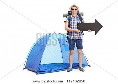 Young male camper standing in front of a blue tent and holding a big black arrow pointing right isolated on white background