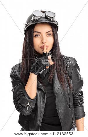 Vertical shot of a female biker holding a finger on her lips and looking at the camera isolated on white background