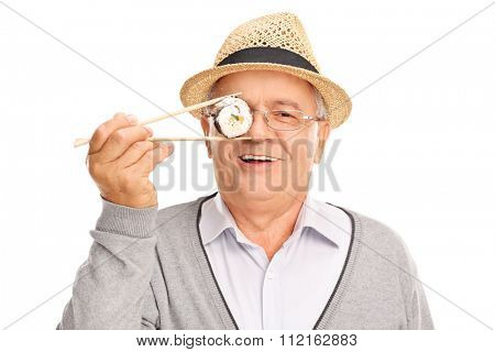 Joyful senior gentleman holding a piece of sushi in front of his eye and looking at the camera isolated on white background