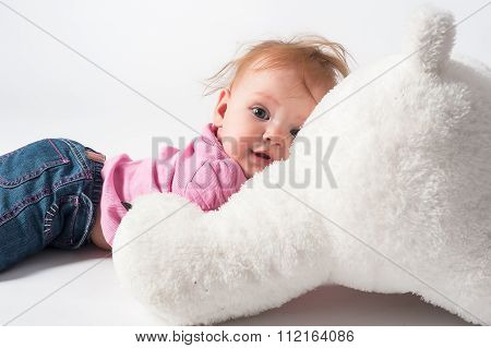 Baby girl plays with white bear toy