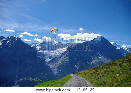Paraglider over A Dirt Road In The Swiss Alps With Mountain Peaks In The Background