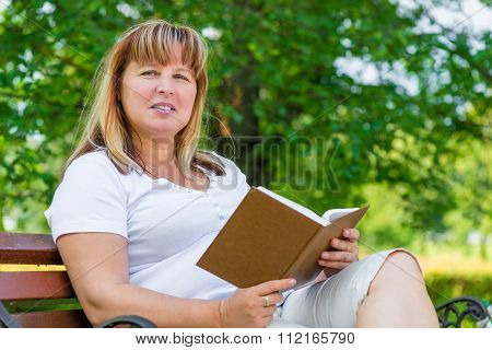 Woman With An Interesting Novel In The Park On A Bench