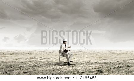 Young businessman sitting in chair with book in hands looking at watch on hand