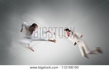 Young determined karate man fighting with businesswoman in suit
