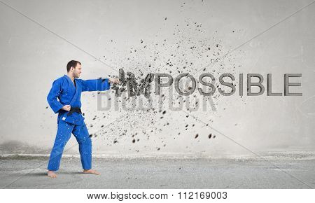Young determined karate man breaking stone impossible word