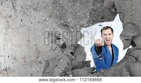 Young determined karate man breaking with hand concrete wall