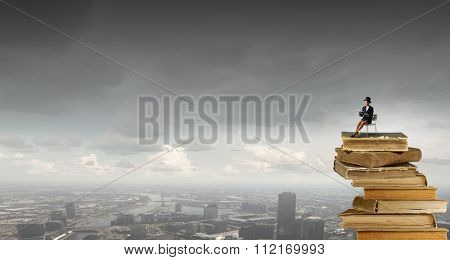 Pretty girl wearing retro hat sitting on chair with book in hands