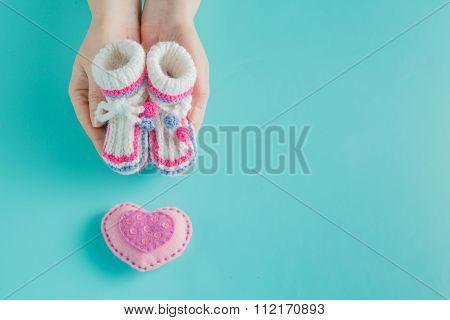 Hand Holding Tiny Knitted Booties