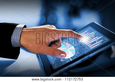 Close up of finger touching blue toned screen on tablet pc