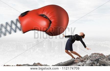 Boxing glove on spring striking businesswoman down