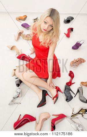 girl in red dress sitting on the floor. Selects shoes. Trying on shoes. beautiful sexy blonde