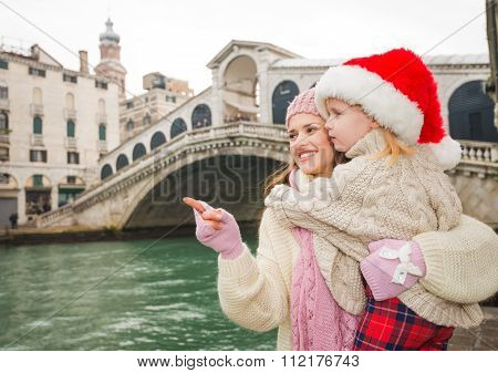 Mother Pointing On Something To Child Wearing Santa Hat, Venice