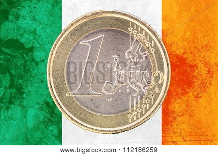 One Euro Coin On The Flag Of Ireland As Background