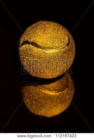 expensive gift gold tennis ball on a black background