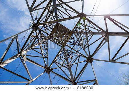 Upward View Of The Structure Under Power Transmission Tower Against Blue Sky