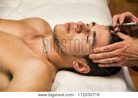 Close-up of young man getting injection of botuline on forehead, laying down with eyes closed