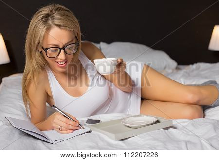 Beautiful woman laying in bed with cup of tea and writing notebook