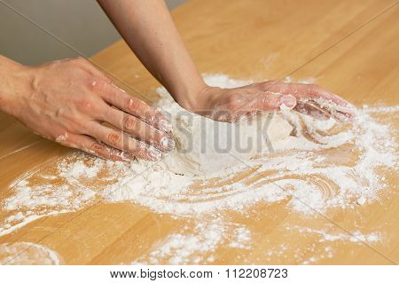 Hands knead the dough