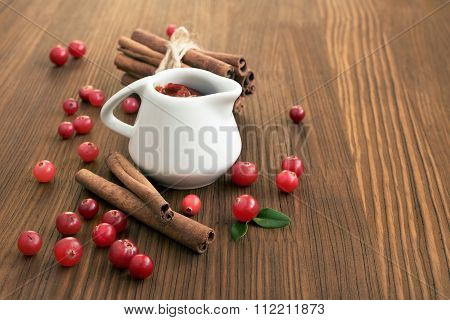 Cranberry sauce with a cinnamon on a wooden table