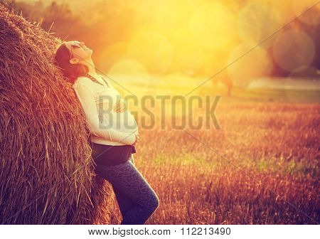 Young Pregnant Woman Standing by the Haystack