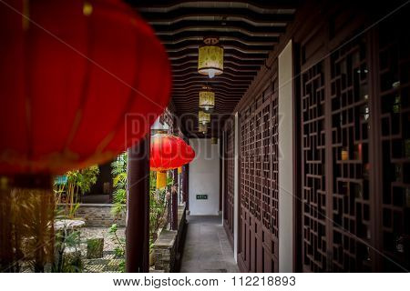 Chinese red lamps on a wooden hallway next to a garden