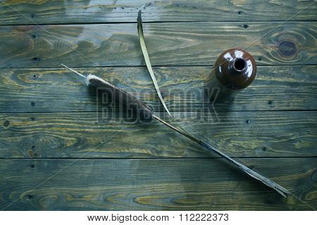 Reed And Clay Bottle On A Wooden Surface
