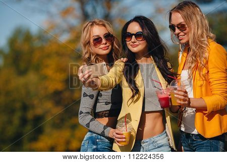 Three girls are walking in the Park in summer and drink fruit juice