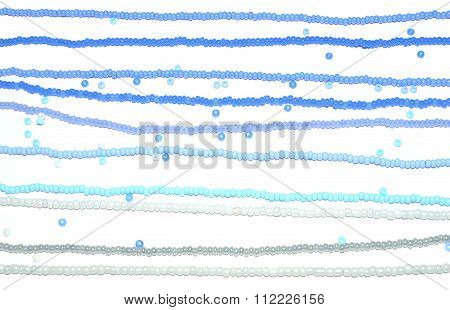 Background of threads with blue, white and silver beads on white