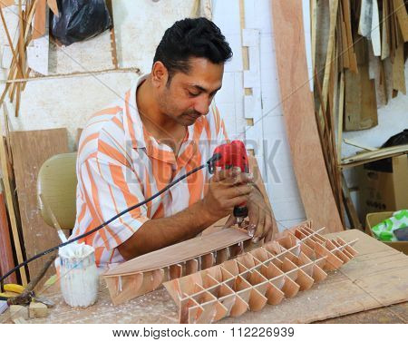 CUREPIPE, MAURITIUS ISLAND - 28. OCTOBER, 2015: Unidentified Creole worker making souvenirs (ship models) for visitors of Mauritius. Traditional handicraft.