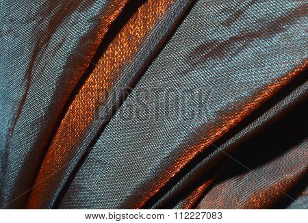 Iridescent fabric chameleon in orange, brown and purple colors, texture, background