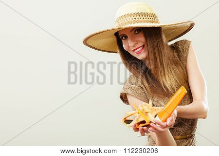 Woman Holds Sunglasses And Sunscreen Lotion