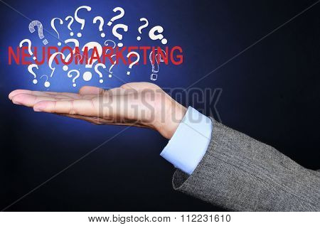 closeup of a young caucasian businessman with the word neuromarketing and a pile of question marks in his hand