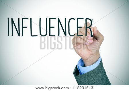 closeup of the hand of a young caucasian man in suit writing the word influencer with a pen in the foreground