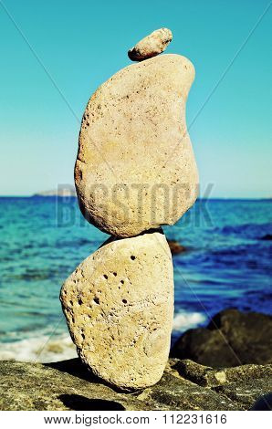 closeup of a stack of balanced stones in Ibiza Island, in Spain, with the Mediterranean sea and in the background