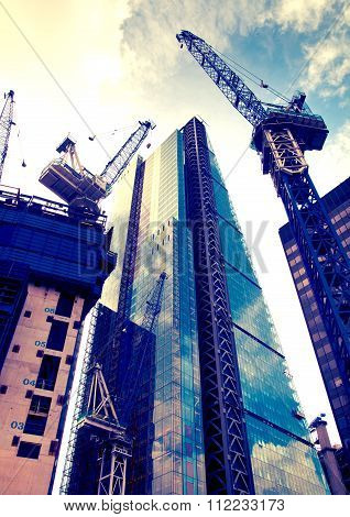 LONDON, UK - DECEMBER 19, 2014: Building site with cranes in the City of London business.