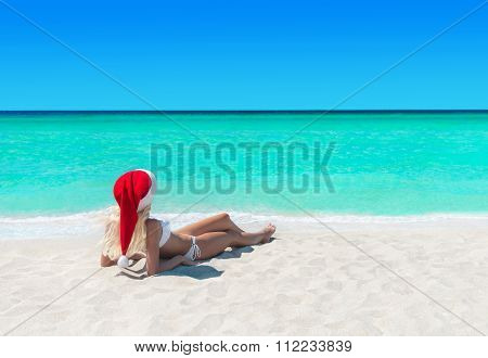 Woman In Christmas Santa Hat Sunbathing At Tropical Ocean Beach