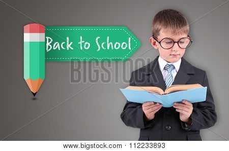 Beautiful little schoolboy with book, on grey background
