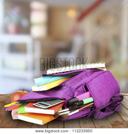 School backpack on wooden desk, on abstract background