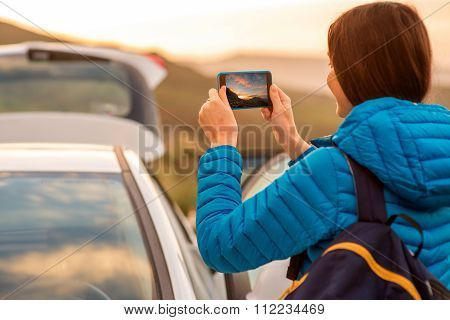 Female traveler photographing sunrise with smartphon near the car