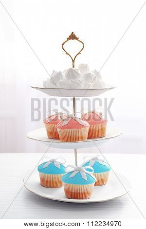 Tasty cupcakes on stand, on light background