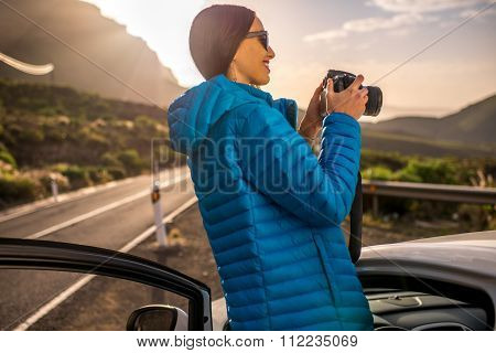 Female traveler photographing sunrise near the car