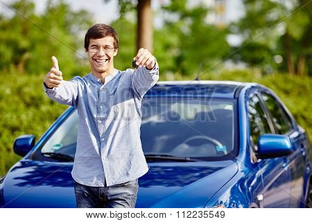 Young hispanic man wearing glasses holding out car keys, showing thumb up hand gesture and smiling against blue car outdoors - new drivers concept
