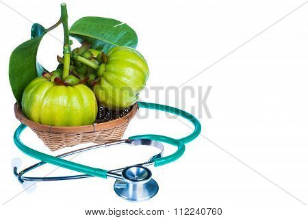 Close Up Garcinia Cambogia And Stethoscope On White Background.