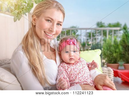 Cute mother with baby sitting on the balcony, young loving family with pleasure spending time outdoors, happy domestic life